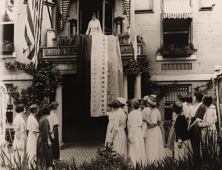 Photograph of Alice Paul standing over ratification banner hanging from the balcony of the National Woman's Party headquarters, with members watching outside the building below.