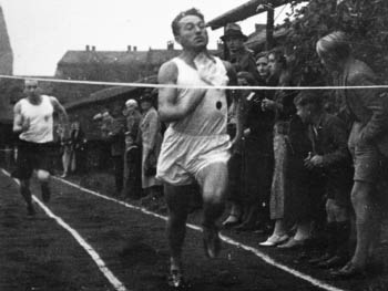 picture of Adi Dassler, founder of Adidas, as a running athlete in 1915, approaching the finished line