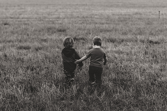 black and white photo of two young brothers holding hands in an open field